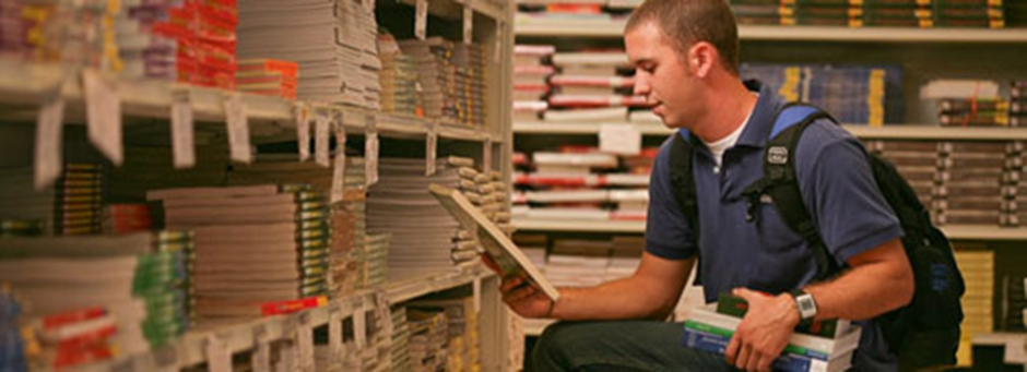 male student looking at book in bookstore