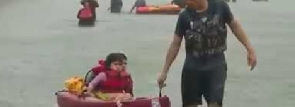rescuer aids a young girl and adult through flooded waters in a kayak