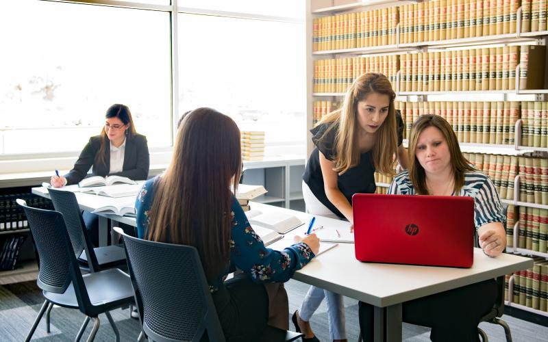 Paralegal students studying in library