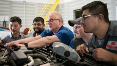 Automotive instructor and students working on a Ford engine