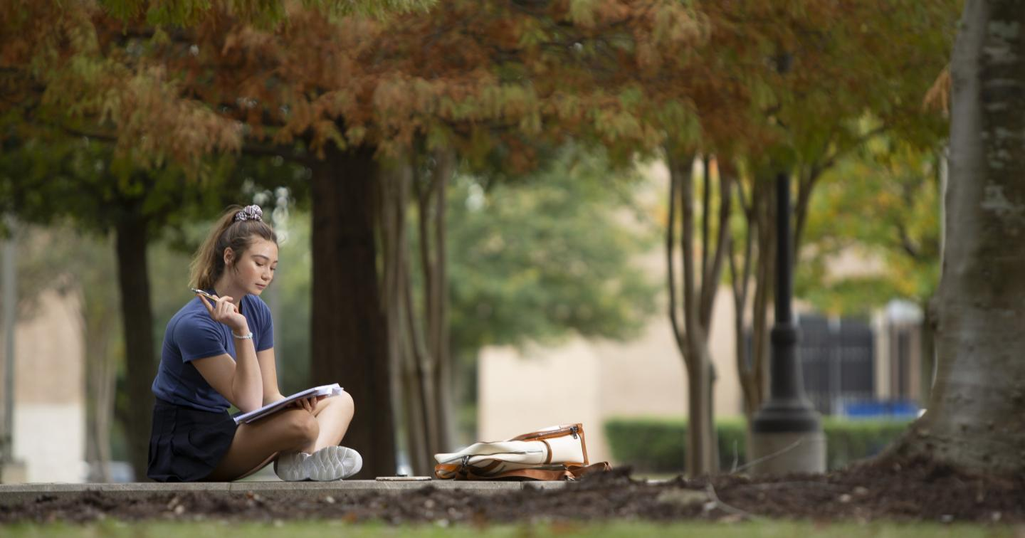 Student sitting outsidte studying