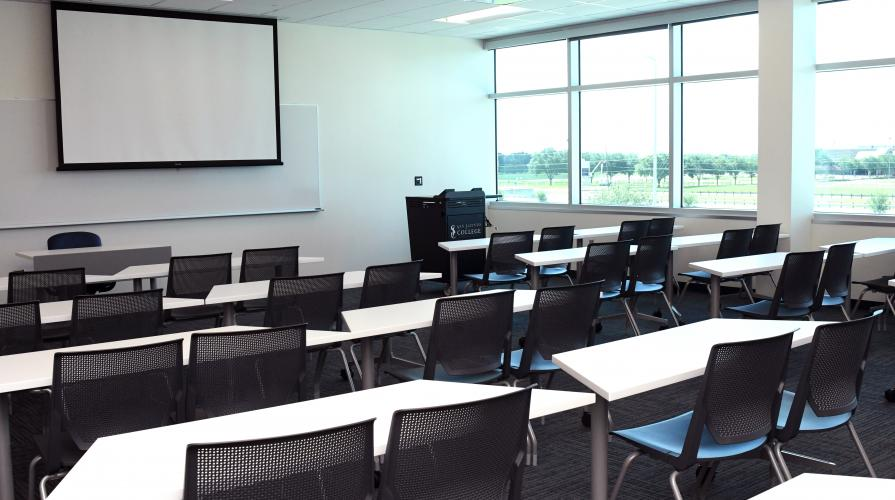 classroom setting with long shared desks facing a display board