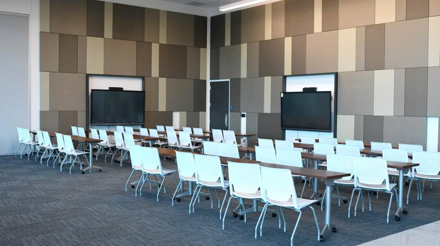 classroom setting with long shared tables in rows facing digital display screens